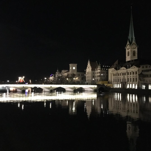 Zurich at night with the canal mirroring the lights.