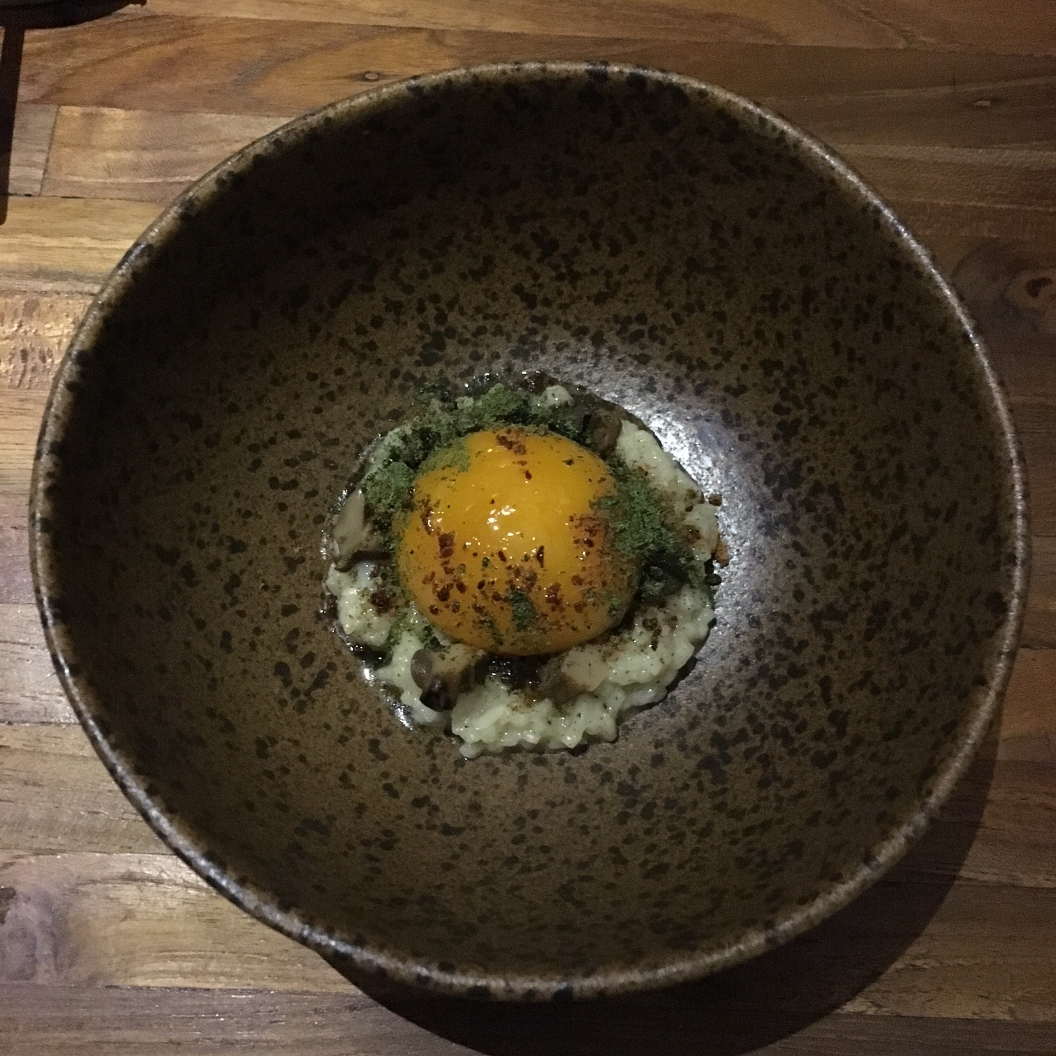 This one is called 'Into The Sawah': Rice porridge from hi-grade rice (from Jatiluwih, Central Bali), snails pressure-cooked in garlic stock, 64-degrees Celsius duck egg yolk, catfish abon, dehydrated fern tips and wild flowers.