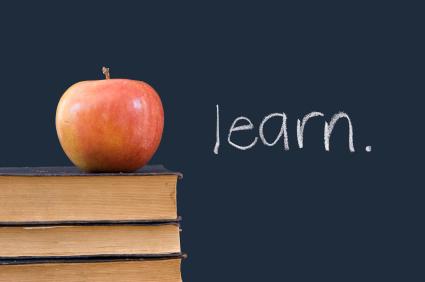 """learn"" written on blackboard with apple, books"