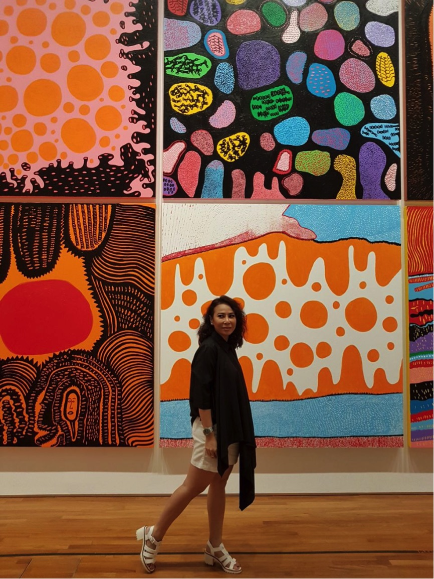 In front of Kusama's pantings that display her love for motifs and colors.